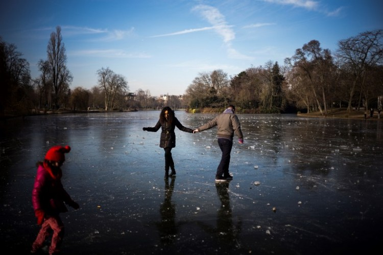 People enjoy the ice on the frozen Daumesnil lake at the Bois de Vincennes park in Paris on January 22, 2017. / AFP PHOTO / LIONEL BONAVENTURE