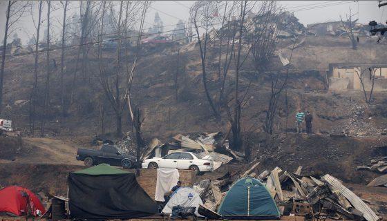 Un grupo de personas descansan en carpas luego de que sus casas fueran arrasadas por un incendio forestal. EFE