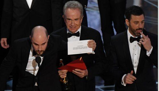 """El actor estadounidense Warren Beatty (C) muestra la carta de la mejor película 'Moonlight' al lado de """"La La Land"""", el productor Jordan Horowitz (L) y el anfitrión Jimmy Kimmel después de leer erróneamente """"La La Land"""" 2017 en Hollywood, California. AFP"""
