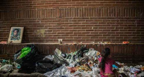 Una muchacha busca alimentos en la basura en un barrio de Caracas. AFP
