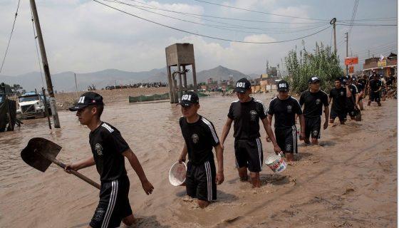 Soldados llevan herramientas para ayudar a los habitantes a cruzar una calle inundada en Lima, Perú. AP
