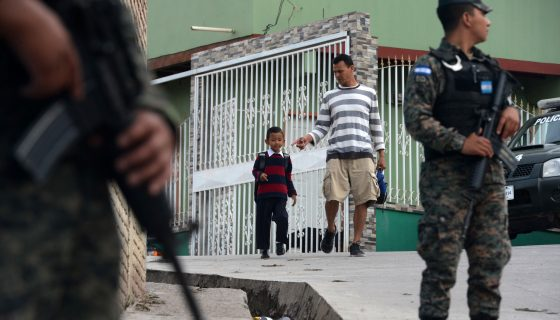 Miembros de la Policía Militar están de guardia cuando los estudiantes llegan a clase en la escuela Maximiliano Sagastume en Sagastume, Honduras. AFP