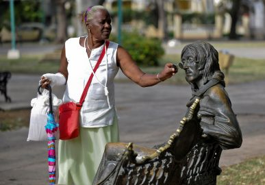 """Una mujer pone anteojos a la estatua del fallecido John Lennon, en un parque de La Habana, Cuba. Lennon perteneció a la reconocida banda británica """"The Beatles"""" en los años 60. LA PRENSA/AFP"""