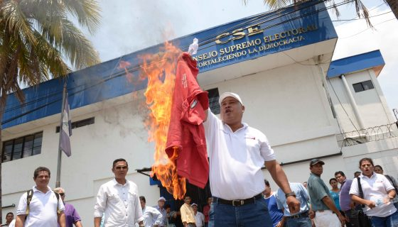 Paulino Zeledón, presidente municipal de CxL en El Viejo, Chinandega, quema una camisa roja con siglas blancas del PLI, frente a una sede del poder electoral. Foto LA PRENSA/Manuel Esquivel